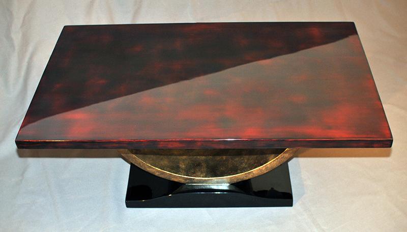 Table de style Art déco – plateau rouge et glacis bruns, piétement en laque arrachée bronze et laque noire.